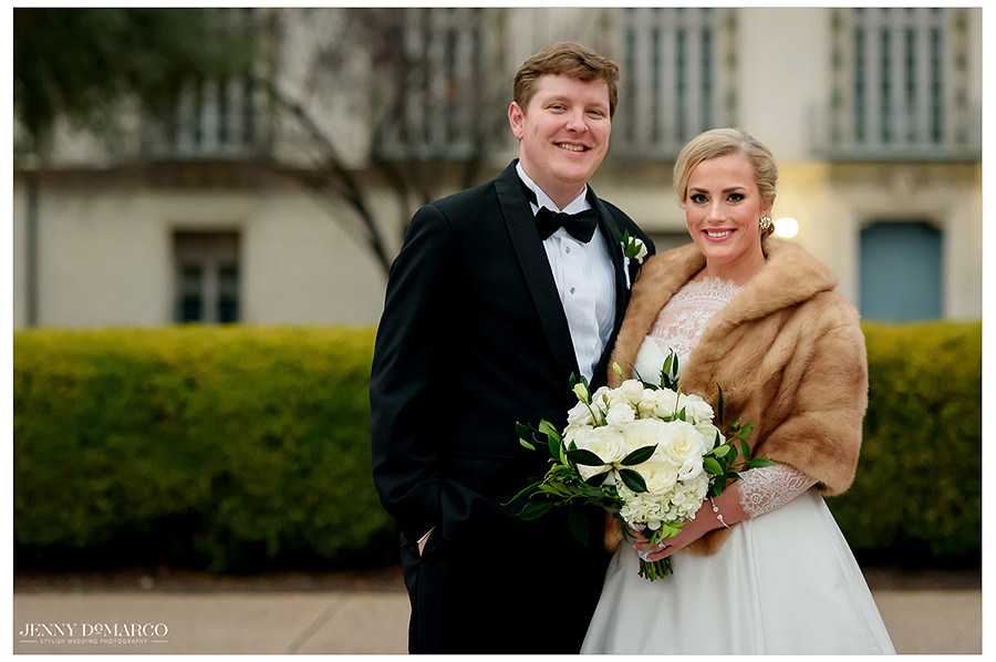 the bride and groom in fur coats in front of the blue exterior