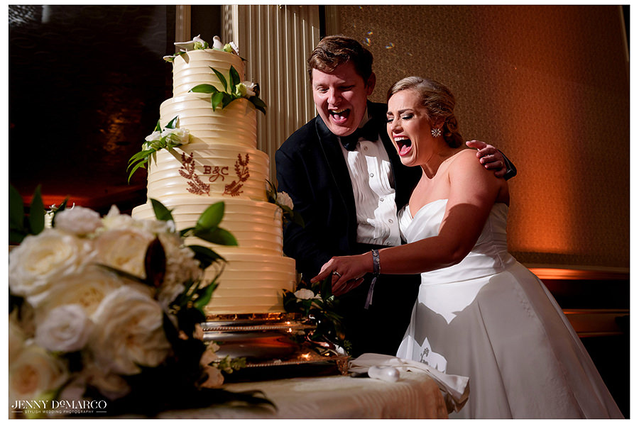 the bride and groom cutting their beautiful cake