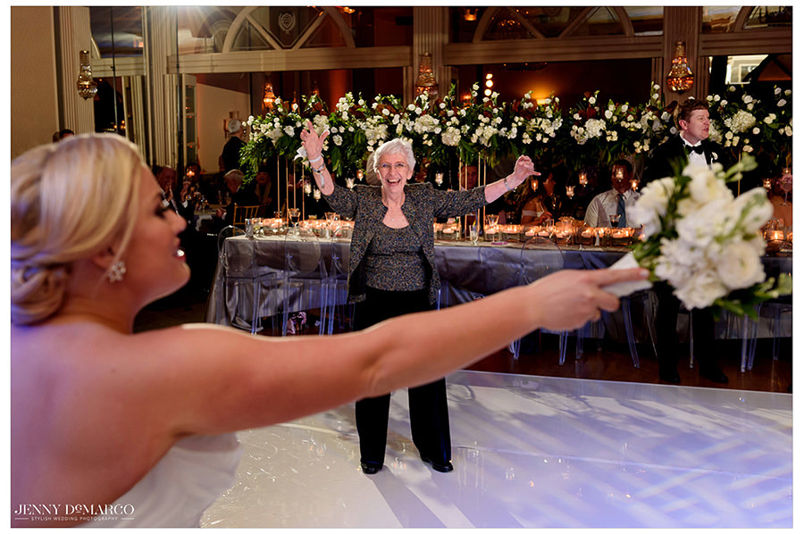 the bride throwing her bouquet and guests cheering