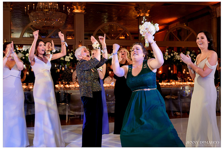 the guests cheering as the bouquet is caught
