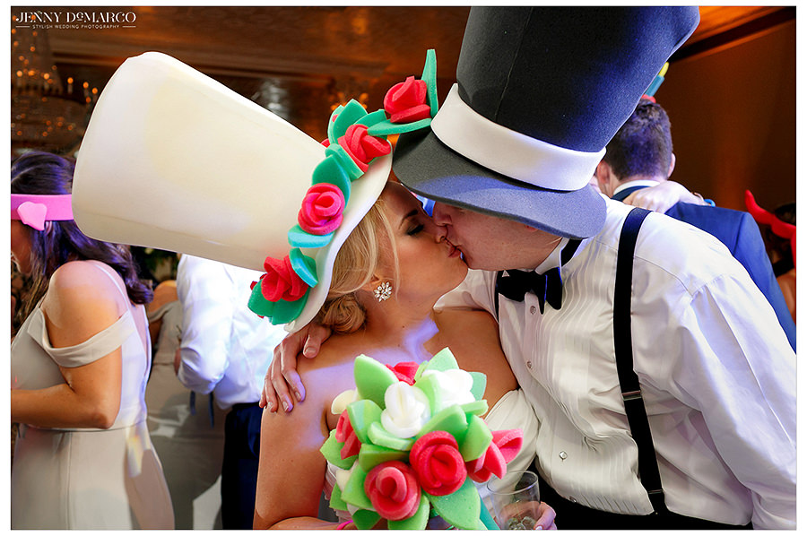 a sweet kiss in funny hates between the bride and groom