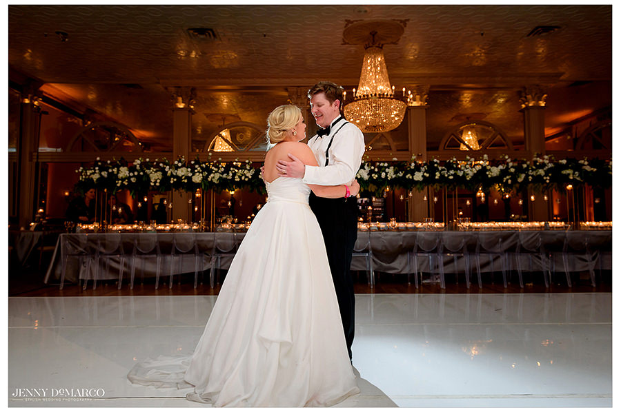 the bride and groom share their last dance under the chandelier at ACC