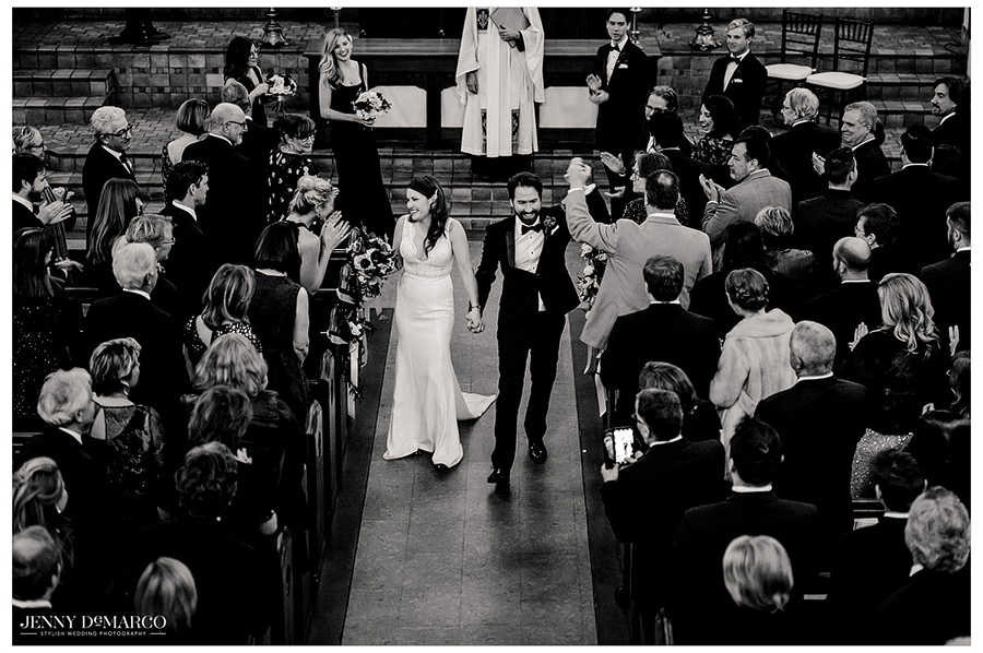 the happy couple leaves the ceremony in elegant black and white shot