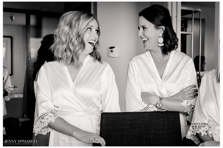 Bride and bridesmaid get ready together in their silk robes.