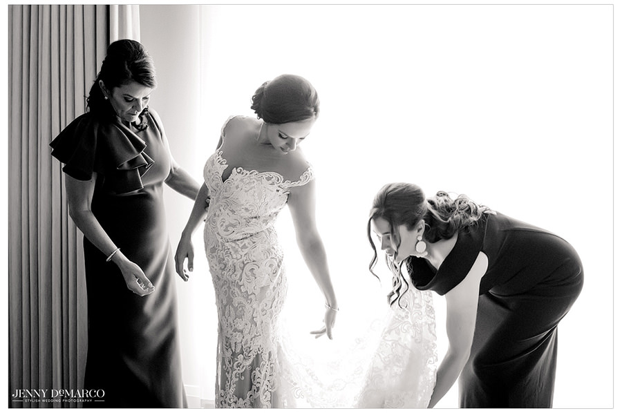 Bride's family helps with the finishing touches of the wedding gown.
