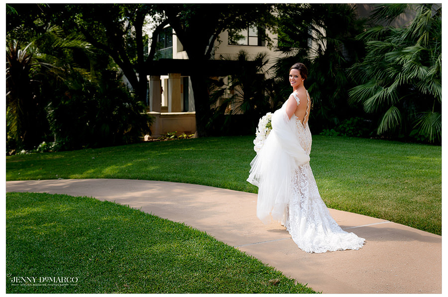 With train in hand, the bride walks along a path outside.