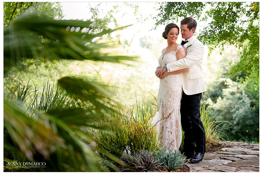 An intimate shot through some foliage of the couple embracing.