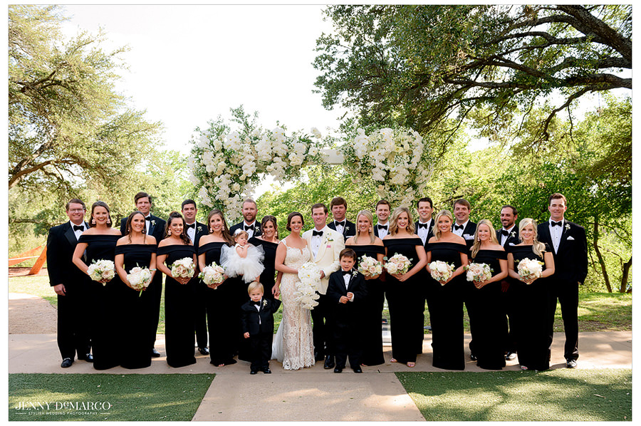 Full wedding party dressed in black and white pose for a picture.