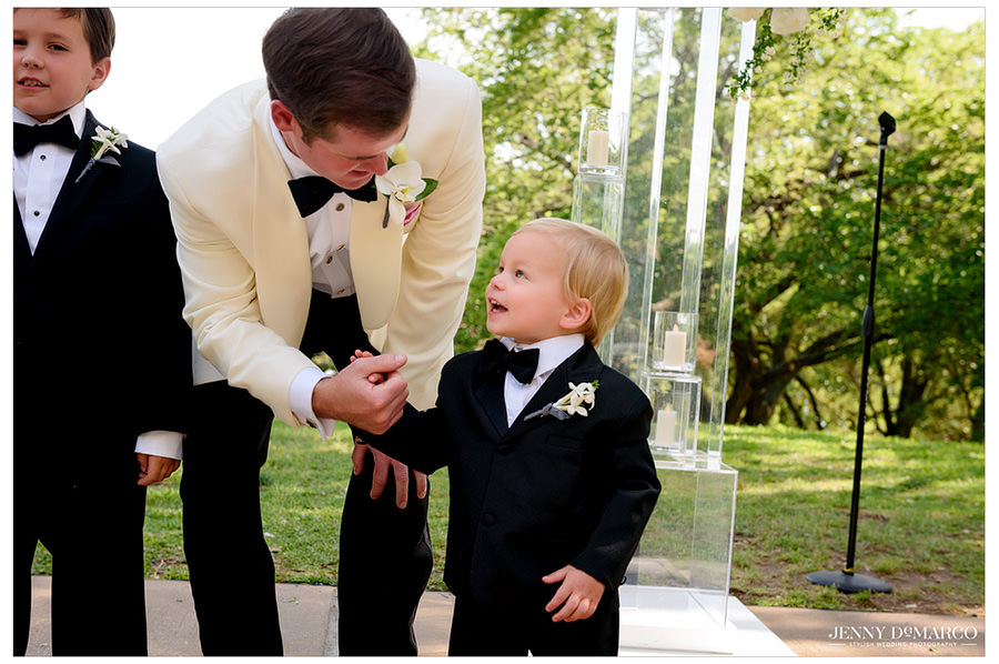 Groom presents the ring bearer with the precious cargo.