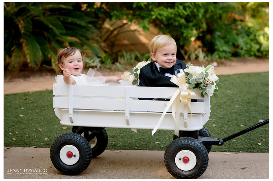 Flower girl and ring bearer ride in style down the aisle in a white wooden wagon.