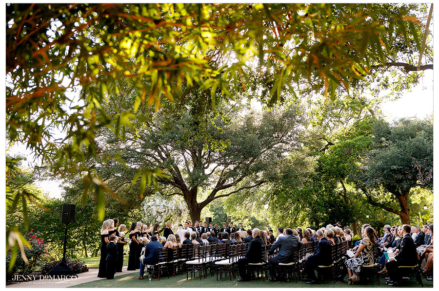 The wedding ceremony takes place outdoors under rich foliage.