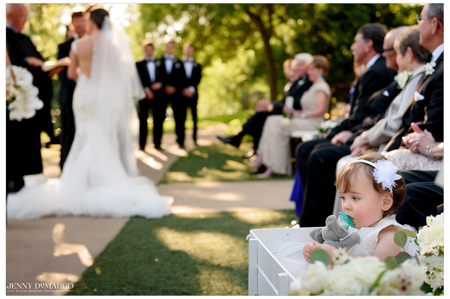 Flower girl sits in her wagon watching the ceremony.