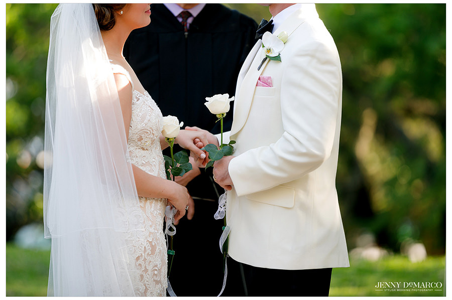 The couple each hold a white rose.