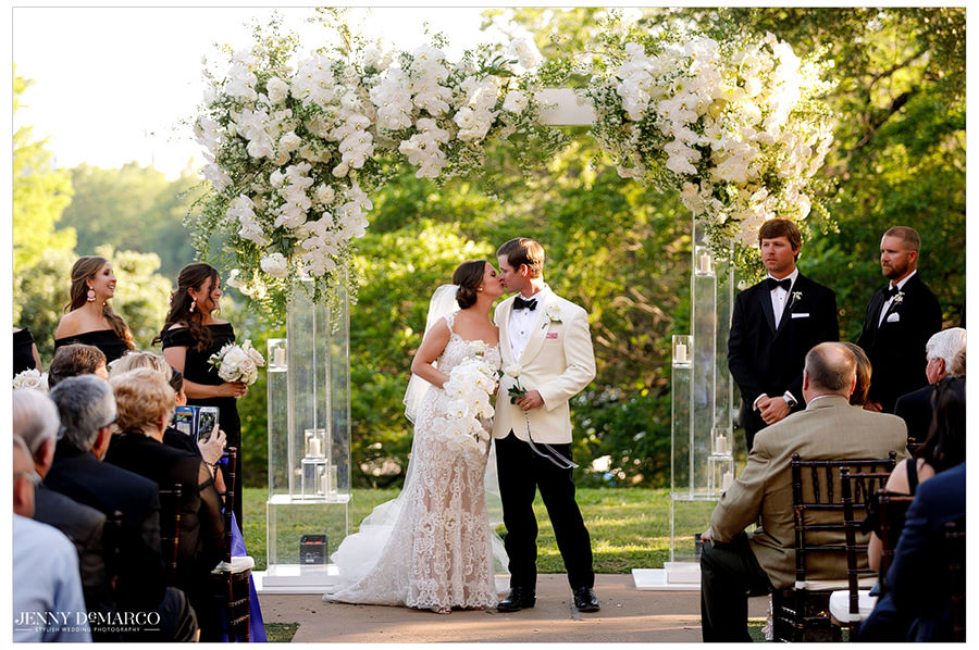 The newlyweds share their first kiss in front of friends and family.