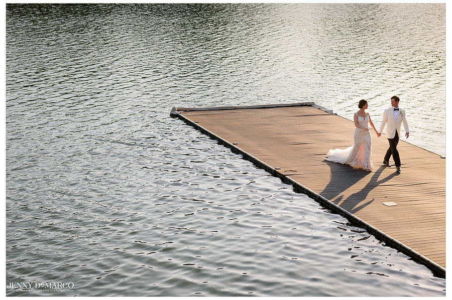 The couple shares a romantic walk on a dock over the lake.