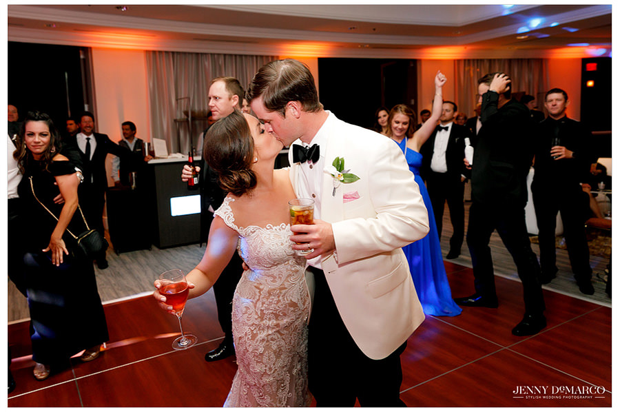 Bride and groom steal a kiss on the dance floor.