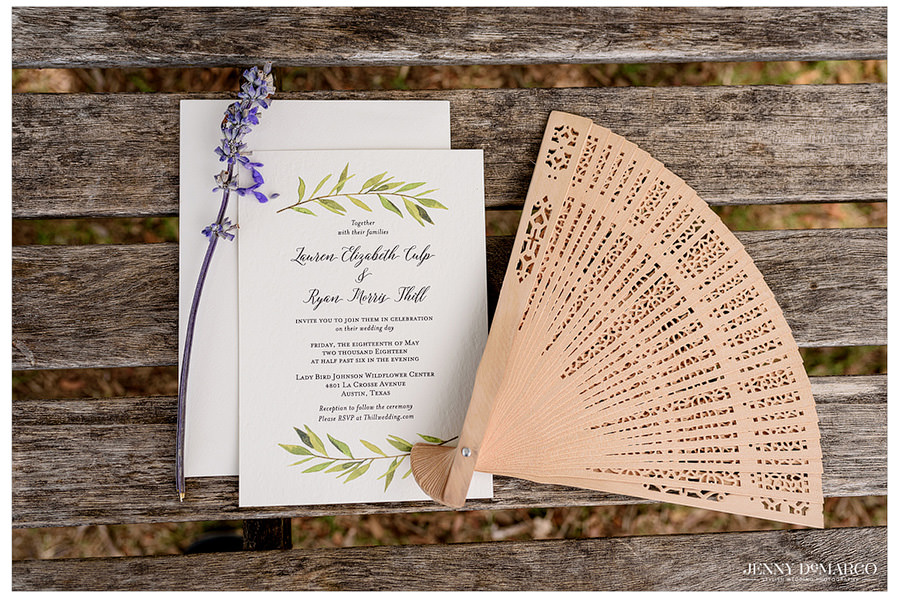 A natural wedding invitation decorated with lavender and a wood hand fan.