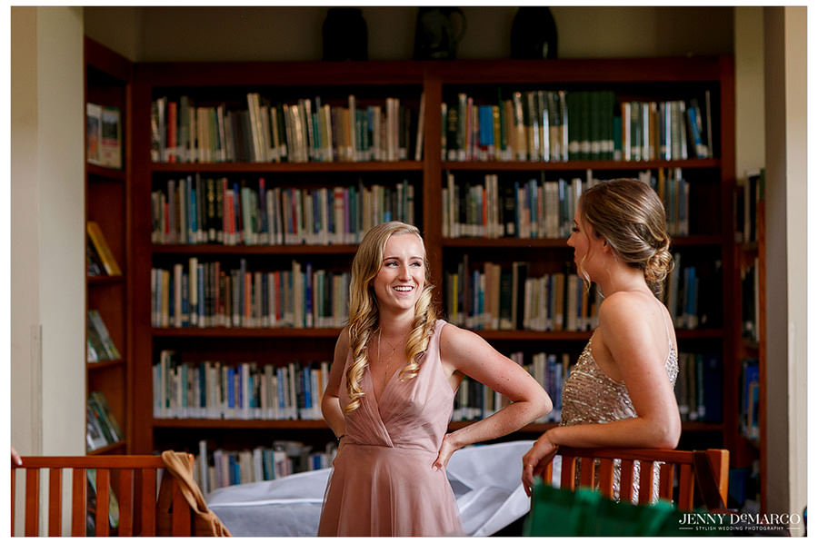 Two brides laugh and talk with each other as they get ready.