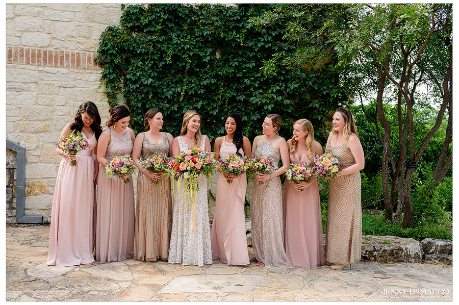 The bride laughs with her bridesmaids as they pose for a picture.