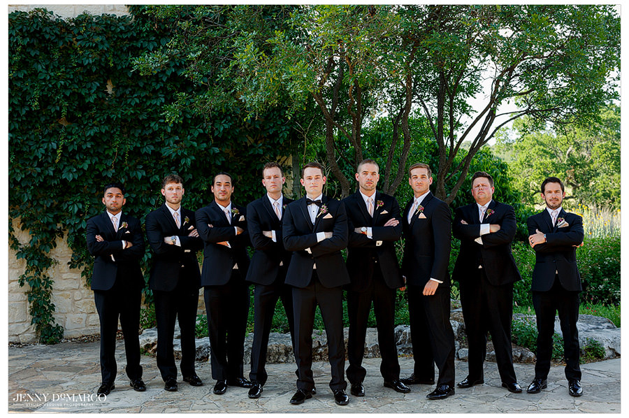 The groom and his groomsmen pose for a band photo in their black tuxes.