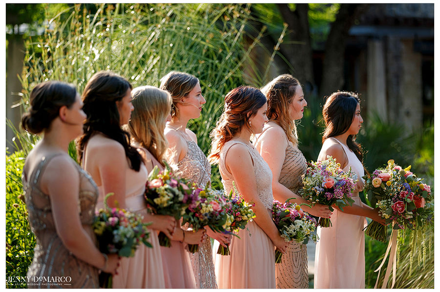 Bridesmaids stand at the front in all different sorts of blush pink dresses.