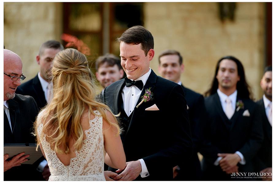 Groom looks giddy as he puts the wedding band on Lauren.