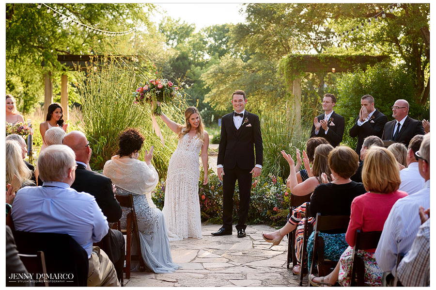 Bride raises her bouquet to her guests after saying yes.