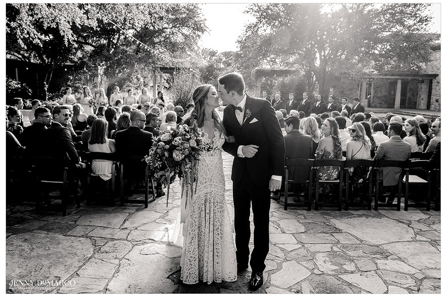 The newlyweds lean in for a kiss after finishing their ceremony.