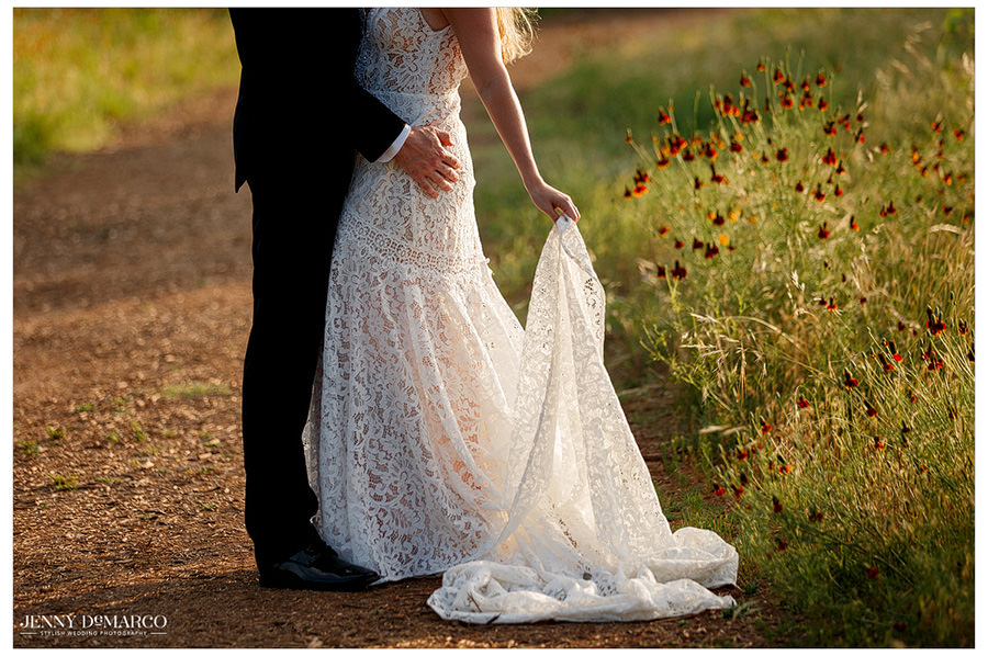 Detail shot of Lauren holding her fully lace dress among the wildflowers.