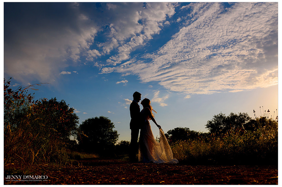 The warm sunset creates a dreamy silhouette of the couple embracing one another.