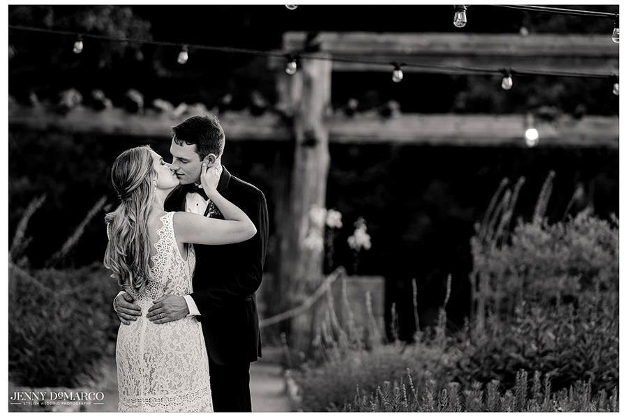 A black and white photo of the newlyweds kissing.