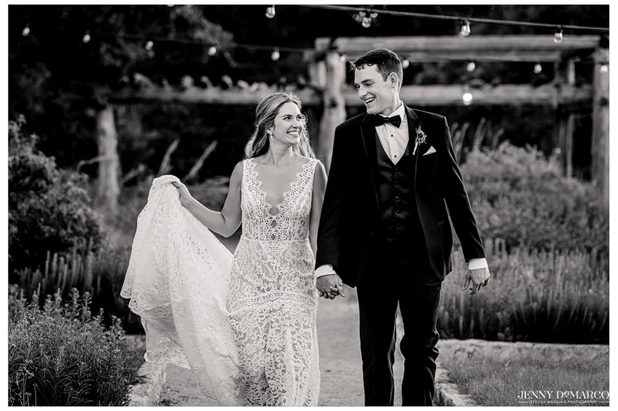 Lauren and Ryan walk under a path lit with string lights.