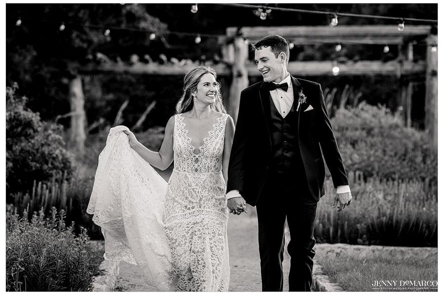 Lauren and Ryan walk under a path lit with string lights.