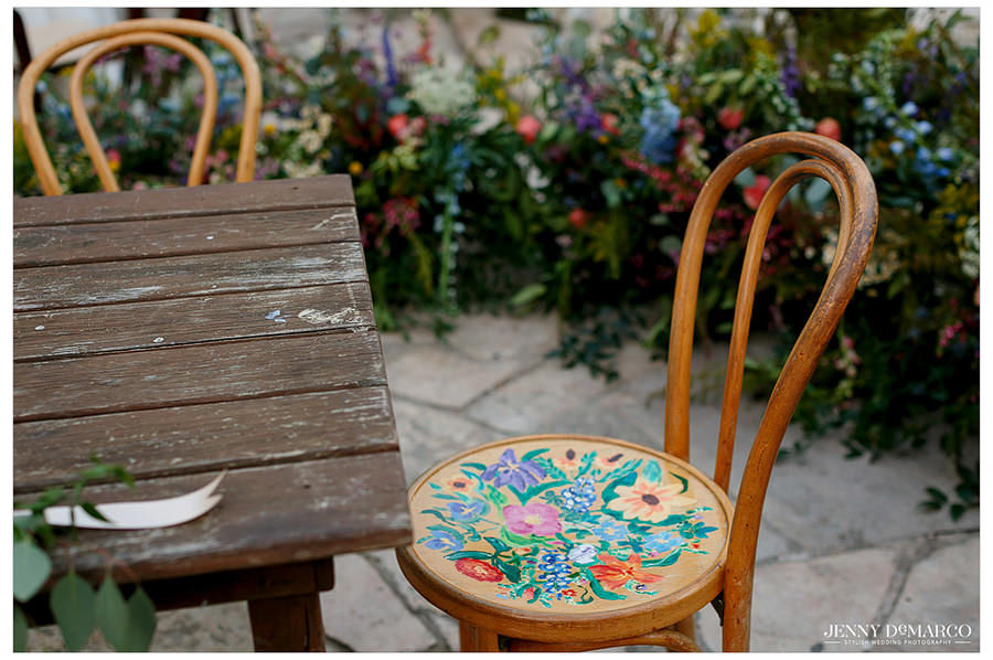 Detail shot of a floral chair for the guests among bright wildflowers.