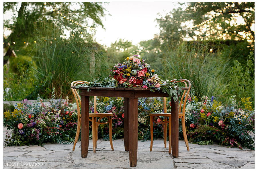 A colorful bouquet of flowers rests on top of a table accenting the nearby wildflowers.