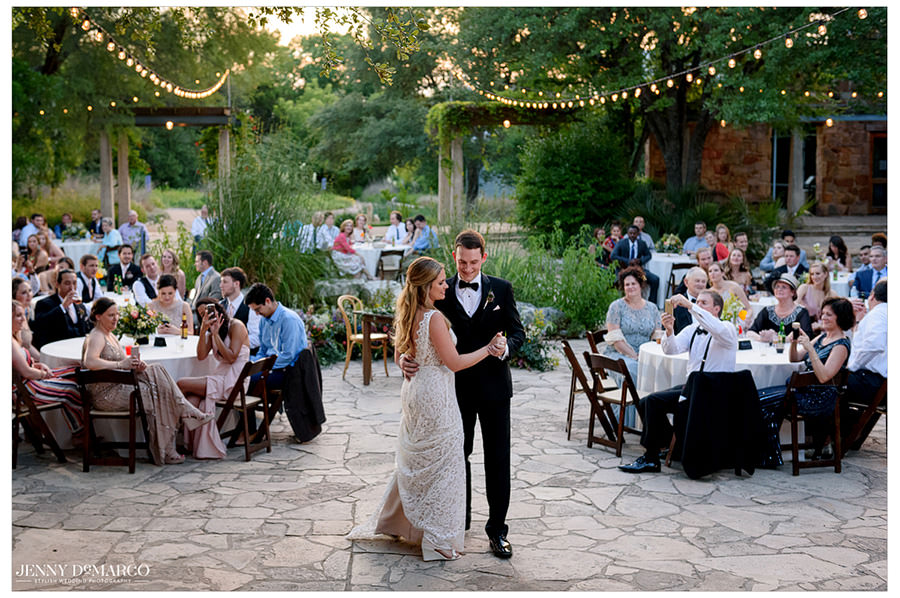 The couple shares their first dance as their guests watch.