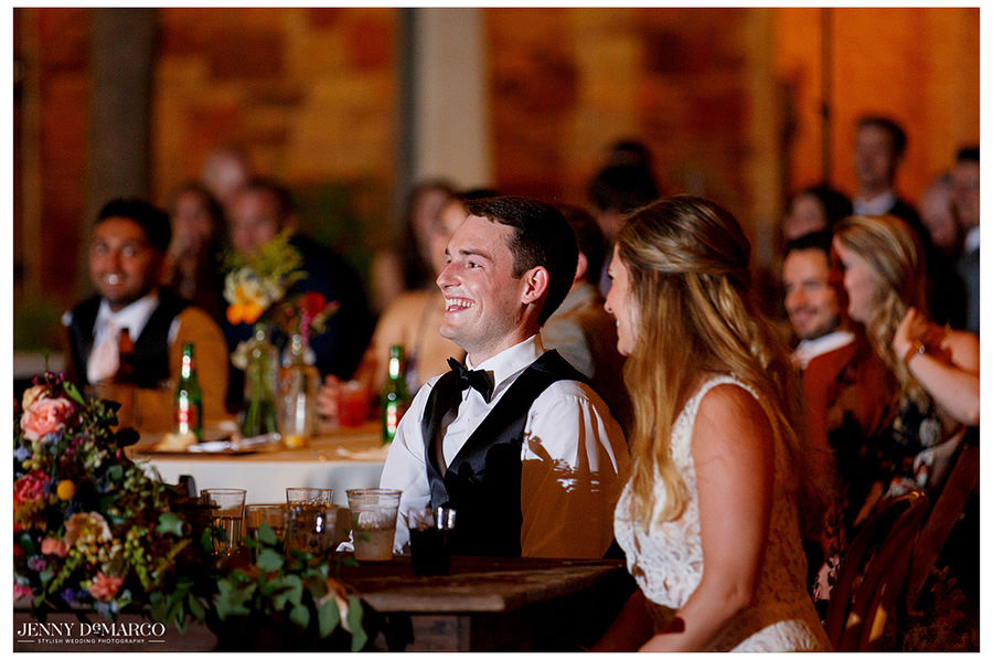 Bride and groom enjoy wedding toasts given by guests as the reception continues.