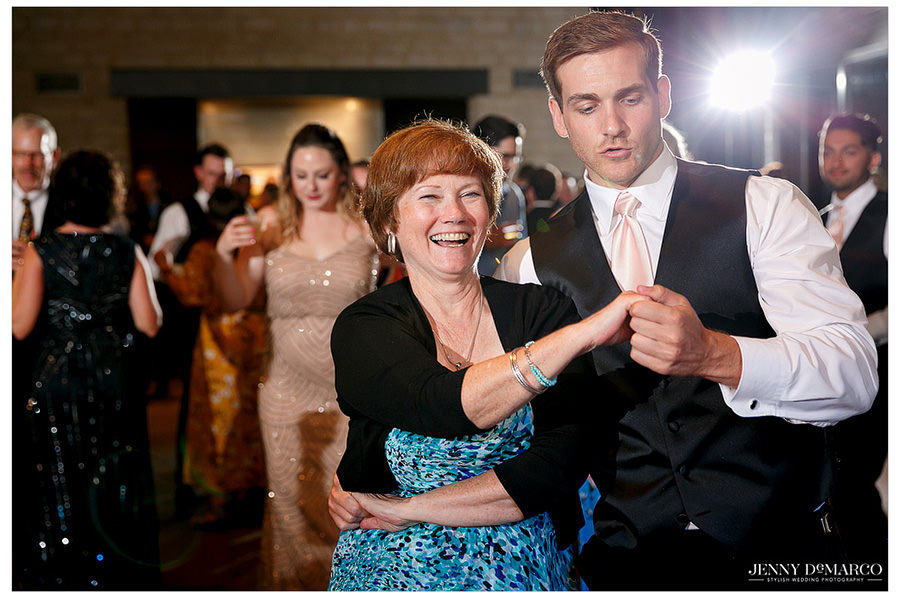 Wedding guests celebrate the couple by showing off their best dance moves.