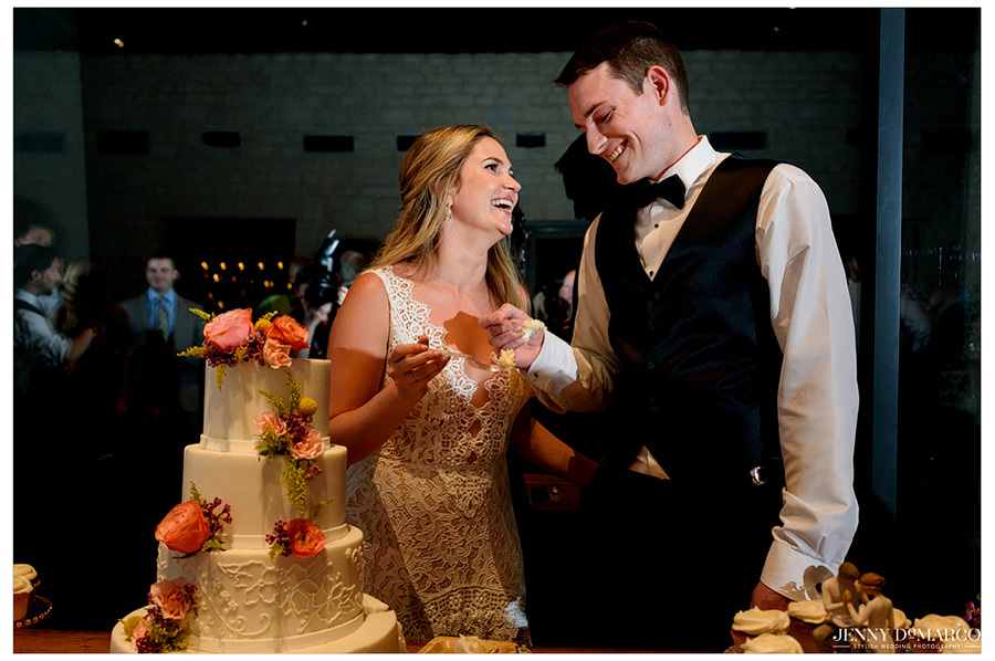 The newlyweds cut their cake thats accented with flowers and begin to eat it.