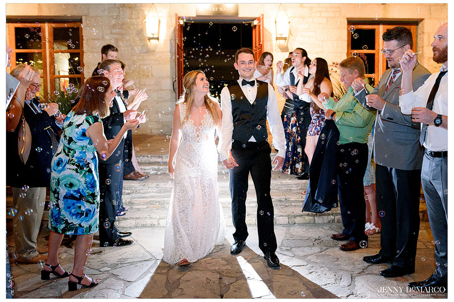 A sea of bubbles sends off the couple as guests cheer for them.