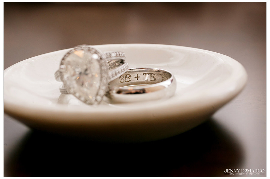 Wedding bands engraved with the couple's initials rest in a small tray.