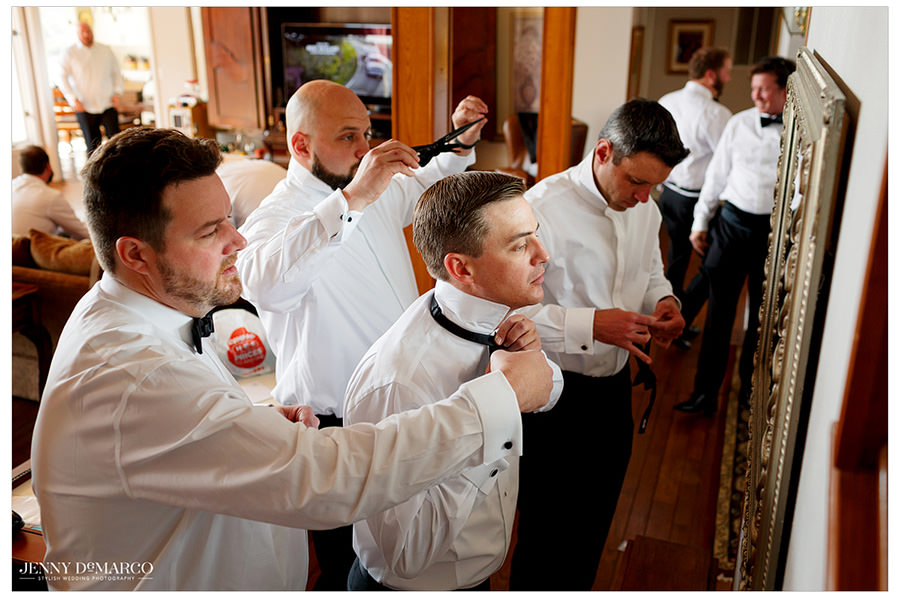 Groomsmen look in the mirror as they all put on their bowties.