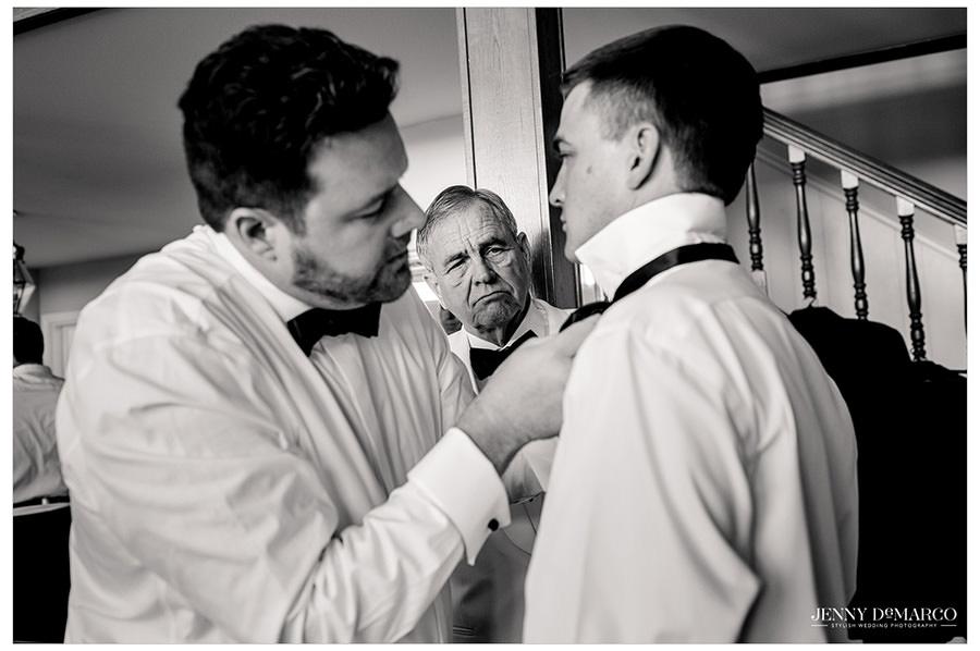groomsmen help Tyler tie his bowtie.