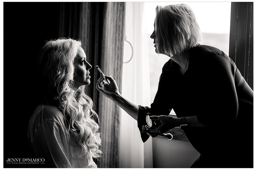 Makeup artist adds some final touches to the brides makeup.