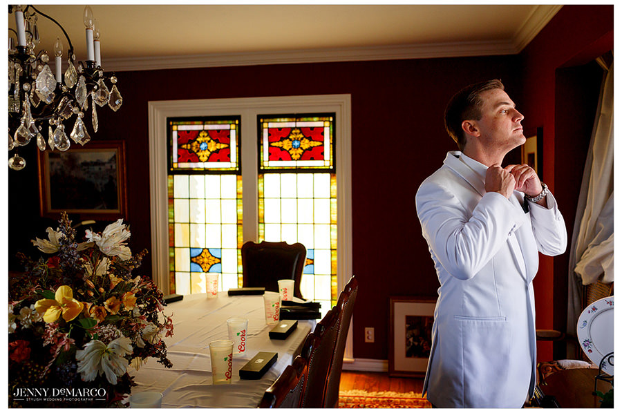 Groom gazes out a window as he puts on his final touches.