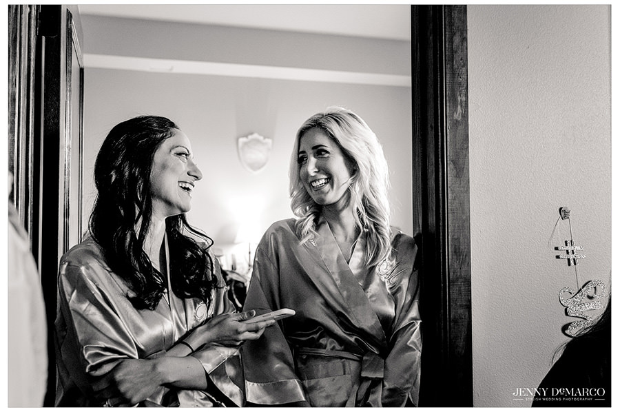 Bridesmaids share a laugh in their satin robes as they get ready.