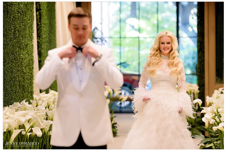 Sheridan walks down an aisle filled with white lilies first her and Tyler's first look.