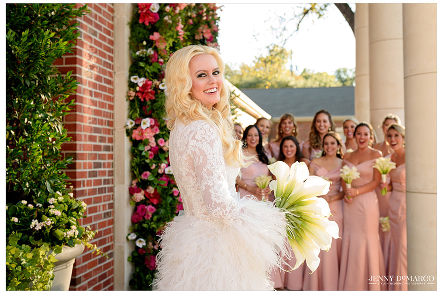Bridesmaids cheer for the bride as she shows them her dress for the first time.