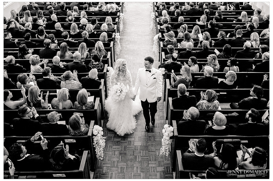 A black and white photo of Sheridan and Tyler walking down the aisle to exit the church.