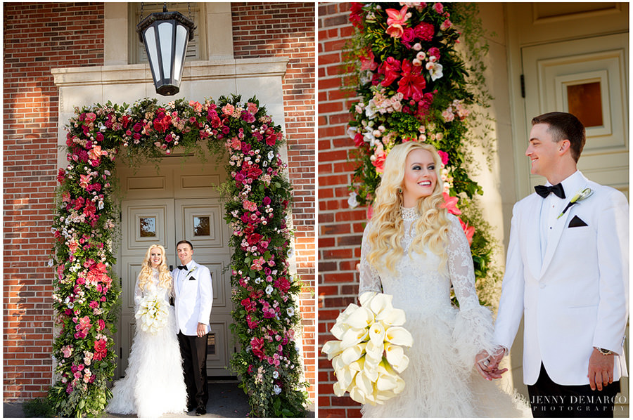 The couple stands under a beautiful arch filled with red and pink roses.